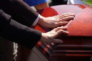 Hands on coffin during funeral prior to burial