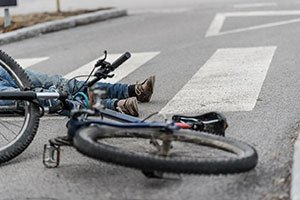 Man and his bike on the ground after being hit by an automobile.