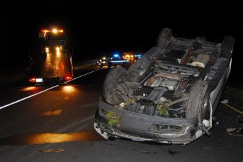 car on its back on highway at night with police in background