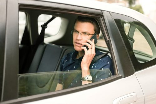 man sitting in backseat on phone