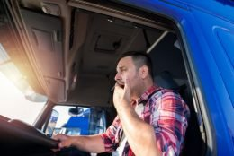 male truck driver behind the wheel yawning