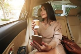 woman drinking coffee with phone in hand sitting in the back seat