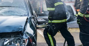 firefighters breaking through a car door with a hydraulic rescue tool