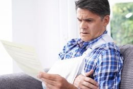 Unhappy older man wearing an arm sling and reading a document